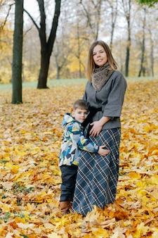 Zoon knuffels moeder in herfst park. moeder en zoon knuffelen in het park in de herfst