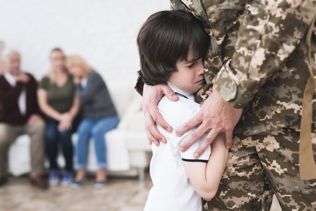 Zoon knuffelt vader die naar het leger gaat.