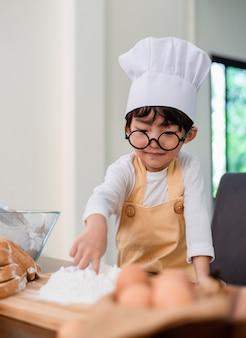 Zoon koken van voedsel. voorbereiding van een ingrediënt met bloem en brood. kid dagelijkse levensstijl thuis. aziatische familie in de keuken.