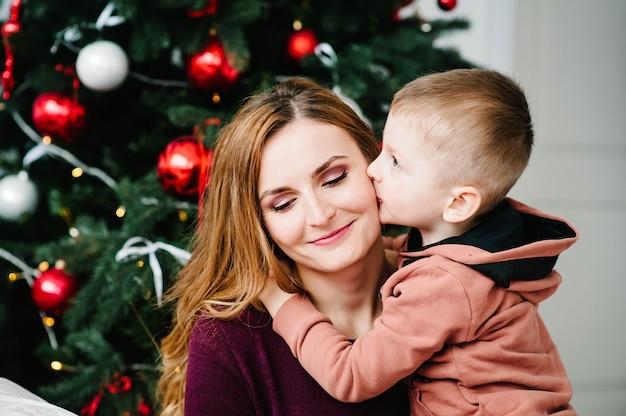 Zoon kust moeder bij de kerstboom gelukkig nieuwjaar en vrolijk kerstfeest