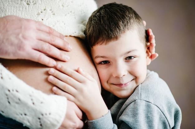 Zoon luistert naar de buik van zijn mooie zwangere moeder en lacht