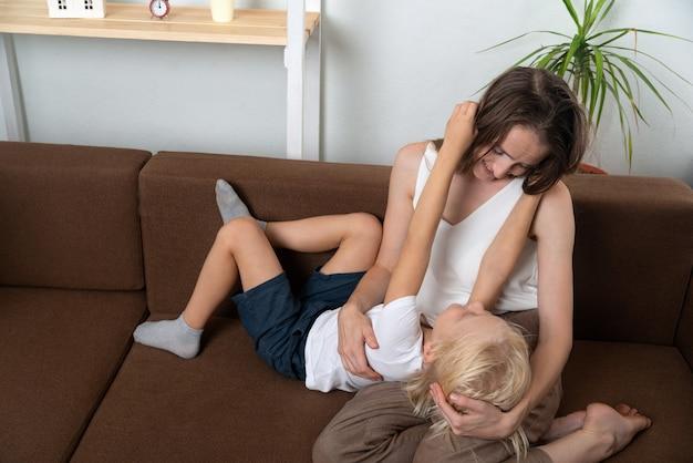 Zoon met moeder chat en knuffel. moeder en zoon spelen thuis.