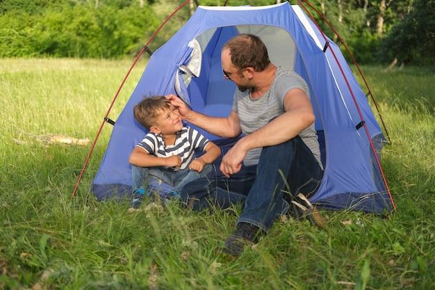 Zoon met vader zit en praat in tent in de natuur. vrije tijd met vader, ouderschap. familie kamperen. gelukkige familiewandeling in de zomer. reizen met kinderen