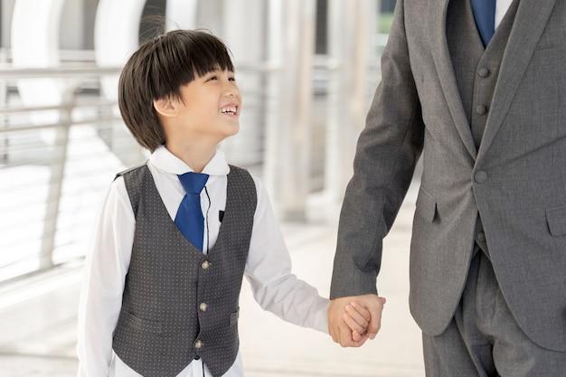 Zoon met vaders hand op zakenwijk stedelijk