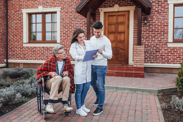 Zoon met verpleegster die over oude man in rolstoel praat en naar zijn resultaten kijkt
