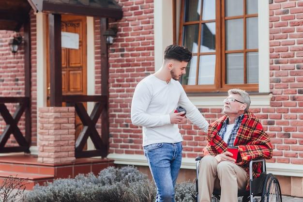 Zoon met zijn vader die koffie vasthoudt en met papa praat