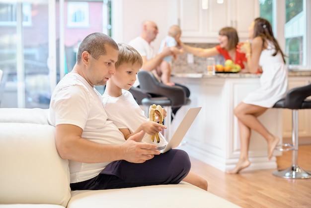Zoon met zijn vader zittend op de bank, kijkend naar de laptop, een kleine jongen die een banaan eet, in de keuken moeder vrienden en baby