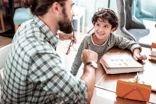 Zoon onderwijzen. bebaarde vader die vierkant overhemd draagt dat boek in restaurant onderwijst zoonbrieven