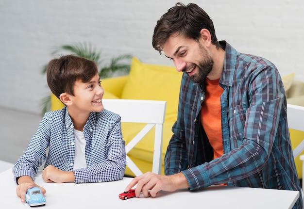 Zoon speelt met speelgoedauto's en kijkt naar zijn vader
