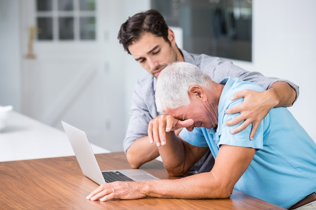 Zoon troostende gespannen vaderzitting bij bureau