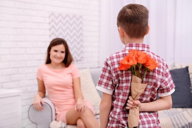 Zoon verbergt rozen voor zijn moeder achter zijn rug