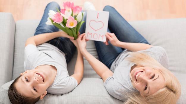 Zoon verrassende moeder met bloemen en kaart