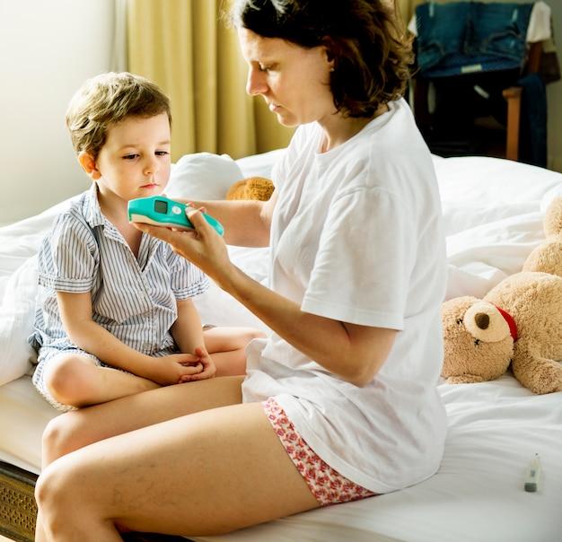 Zoon wordt ziek en zijn moeder controleert de temperatuur