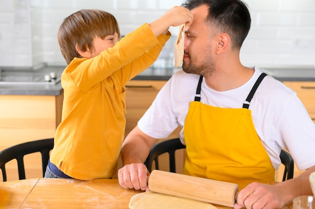 Zoon zet een deegmasker op het gezicht van zijn vader