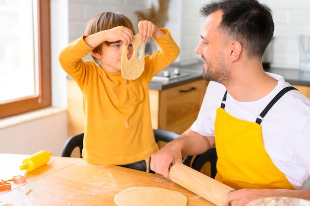 Zoon zet een deegmasker op zijn gezicht