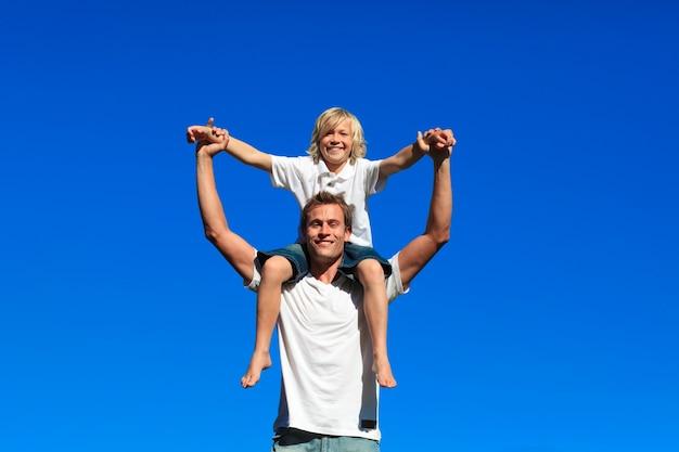 Zoon zit op de schouders van zijn vader