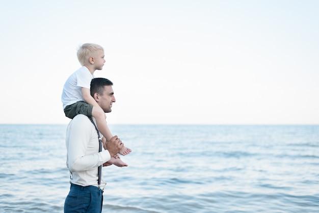 Zoon zittend op de schouders van zijn vader. oudere en jongere broer. man leeftijd concept