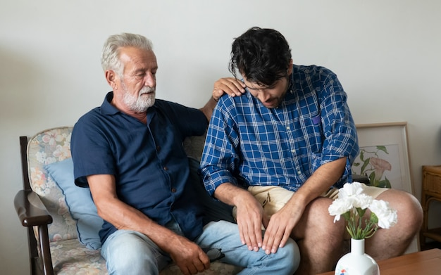 Zoon zorgt senior vader zittend in de woonkamer