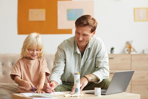 Zoontje aan de tafel zitten en samen met zijn vader tekenen met kleurrijke potloden thuis