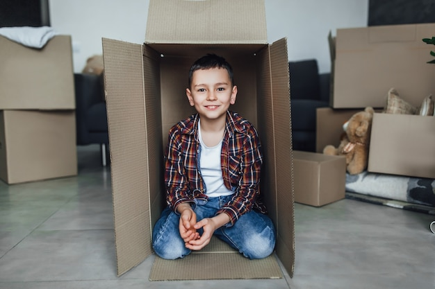 Zoontje blij om in nieuw huis te zijn, met kartonnen dozen in beweging