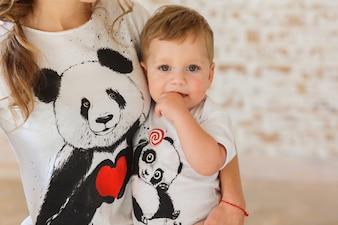Zoontje in de handen van de moeder. Familylook van t-shirts met panda's