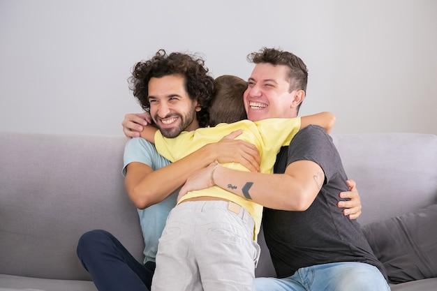 Zoontje knuffelen twee gelukkige knappe vaders thuis. gemiddeld schot. gelukkig gezin en ouderschap concept