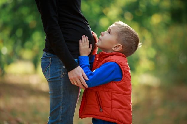 Zoontje knuffels zijn zwangere moeder buik op de natuur. gelukkige jongen raakt een zwangere vrouwenbuik in openlucht in groen park. jonge gelukkige familie wachten baby. zwangere vrouw genieten van tijd met haar kind
