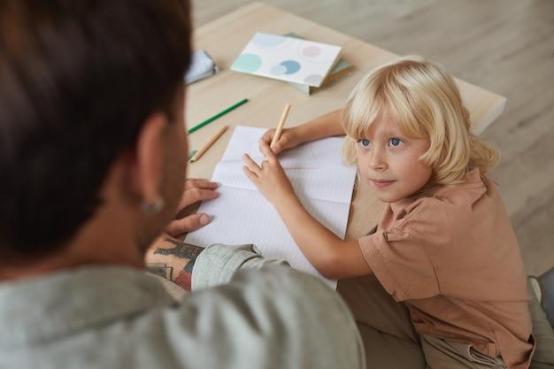 Zoontje met blond haar praten met zijn vader zittend aan tafel en tekenen