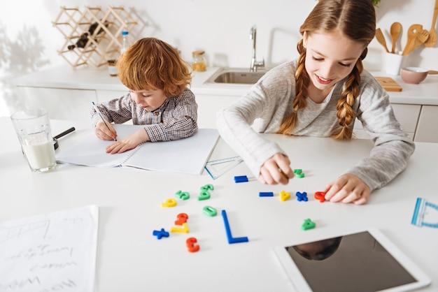 Zorg dragen voor onderwijs. ijverig slim schattig kind dat de formules opschrijft die zijn zus op tafel maakt terwijl ze aan zijn huisopdracht werkt