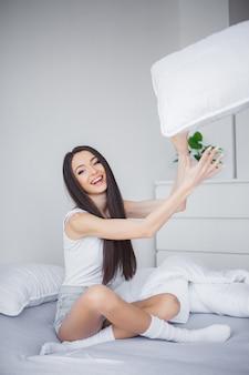 Zorg. een mooie jonge glimlachende donkerbruine vrouw die comfortabel en zalig in wit bed ligt