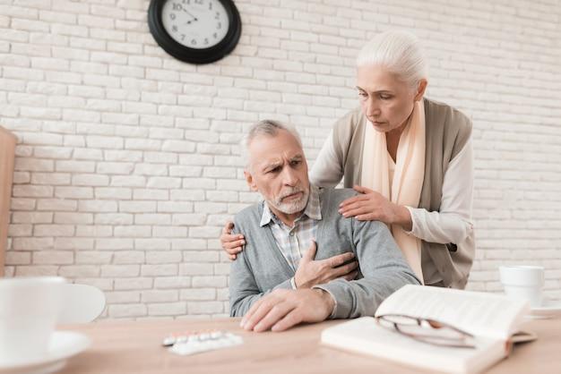 Zorg oude vrouw is bezorgd vanwege pijn in het hart van de man