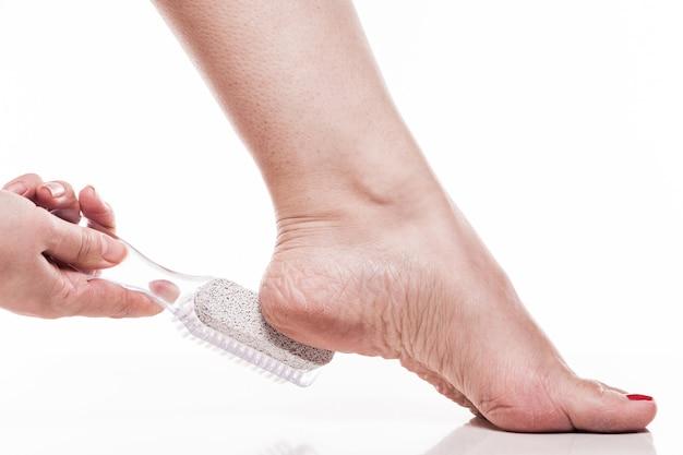 Zorg voor de droge huid op de goed verzorgde voeten en hielen met de hij