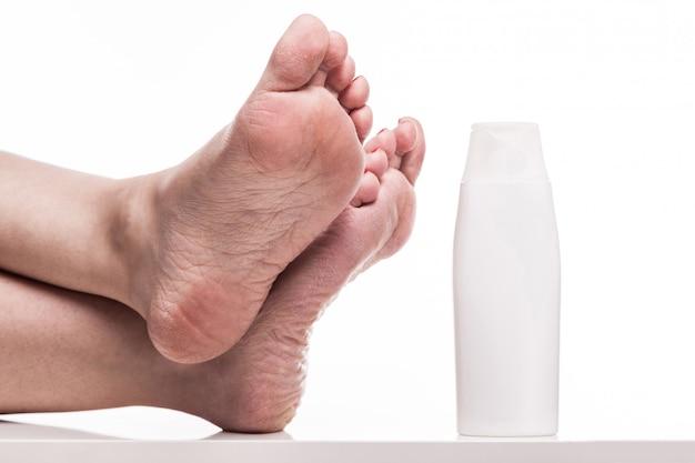 Zorg voor een droge huid op de goed verzorgde voeten en hielen met crèmes
