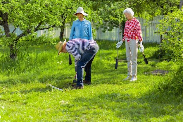 Zorg voor tuin. actieve vriendelijke buren die tuinhuisjes bezitten die samen de tuin verzorgen