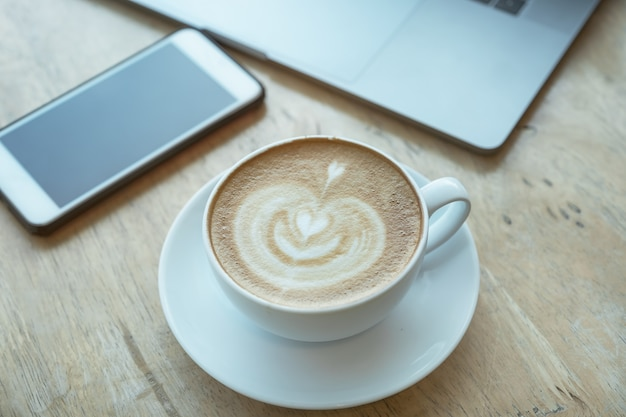 Zorg voor uw gezondheidsconcepten, koffiekop op houten bureau met smartphone en laptop computer in bureau.