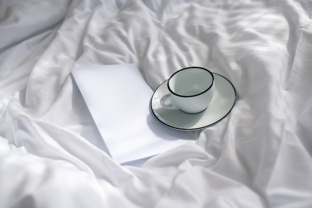 Zorg, welzijn. opgevouwen vel papier met briefje en kop en schotel op verfrommeld schoon wit linnen in zacht daglicht