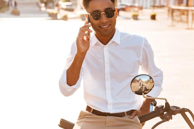 Zorgeloos afrikaanse man in zonnebril zittend op moderne motor buitenshuis en praten door de smartphone