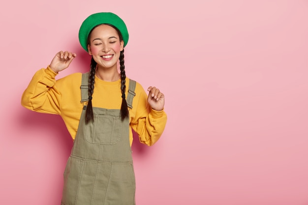 Zorgeloos aziatisch meisje beweegt met het ritme van de muziek, houdt de armen omhoog, draagt een groene baret, een geel sweatshirt en een sarafan