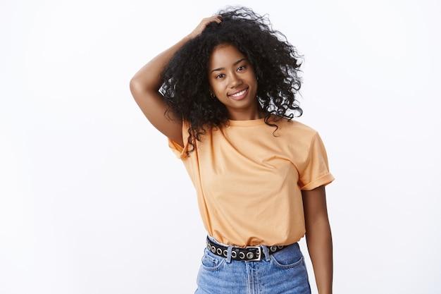 Zorgeloos blij aantrekkelijk jong lichaam-positief meisje met een donkere huidskleur aanraakt krullen afro kapsel kantelend hoofd gelukkig glimlachend beslissend nieuw kapsel, zoals eigen uiterlijk, acceptatieconcept