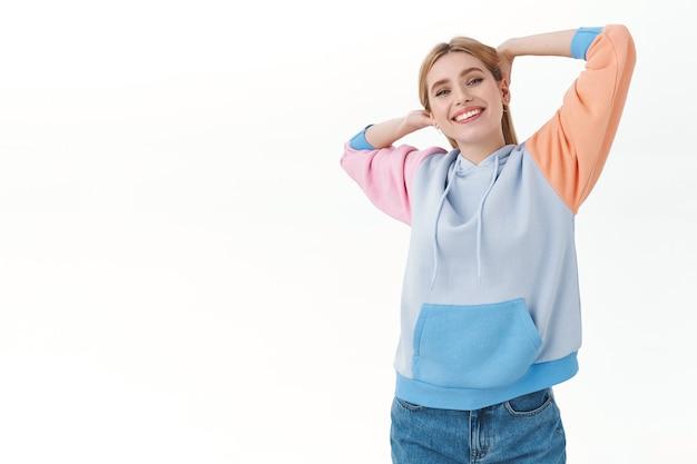 Zorgeloos emoties, lifestyle en vrije tijd concept. portret van gelukkig aantrekkelijk lui blond meisje, die zich uitstrekt na de lunch nap