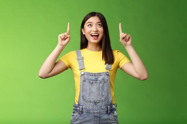 Zorgeloos geamuseerde aziatische brunette in gele t-shirt tuinbroek, glimlachend verbaasd en gefascineerd, kijk omhoog, observeer coole nieuwe promo, grijnzend opgewonden, geniet van het kijken naar de bovenste kopieerruimte.