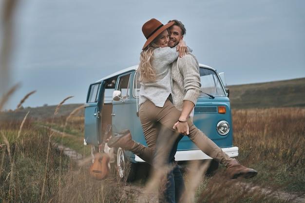 Zorgeloos geluk. mooi jong koppel omarmen en glimlachen terwijl ze in de buurt van de blauwe retro-stijl minibus staan