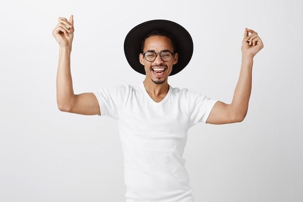 Zorgeloos gelukkig afro-amerikaanse man in hoed en bril, dansende handen omhoog en vrolijk lachen