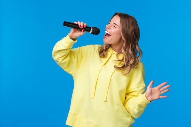 Zorgeloos gelukkig blond europees meisje met plezier, geniet van het zingen van karaoke met hart en hartstocht, ogen dicht met microfoon, blij