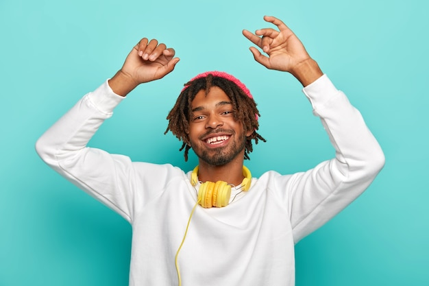 Zorgeloos gelukkig hipster luistert muziek in moderne hoofdtelefoon, heft armen op en danst vreugdevol, voelt zich ontspannen, draagt witte trui, geïsoleerd op blauwe achtergrond