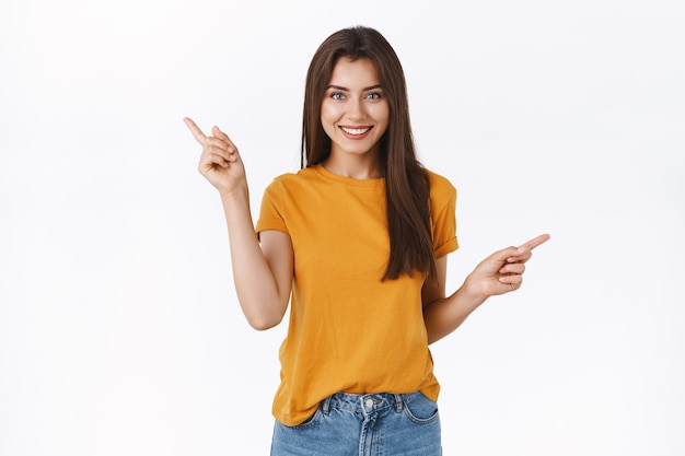 Zorgeloos, gelukkig lachend meisje in geel t-shirt winkelen met zelfverzekerde ontspannen uitdrukking, zijwaarts naar links en rechts wijzend om een keuze te maken, advies of suggesties te vragen wat beter te kopen