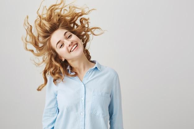 Zorgeloos gelukkig meisje zwaaien hoofd, met haar nieuwe kapsel