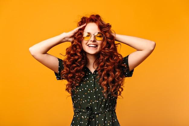 Zorgeloos gembermeisje dat met gesloten ogen lacht. studio shot van extatische jonge vrouw aanraken van krullend haar op gele achtergrond.