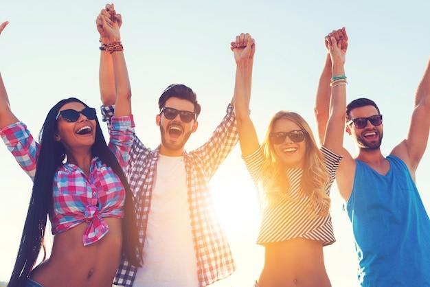 Zorgeloos genieten. lage hoekmening van vier vrolijke jonge mensen die elkaars hand vasthouden en armen omhoog houden terwijl ze tegen de lucht staan