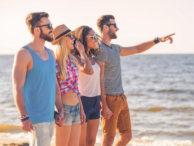 Zorgeloos genieten met vrienden. groep jonge vrolijke mensen die samen langs het strand lopen en glimlachen terwijl een man wijst